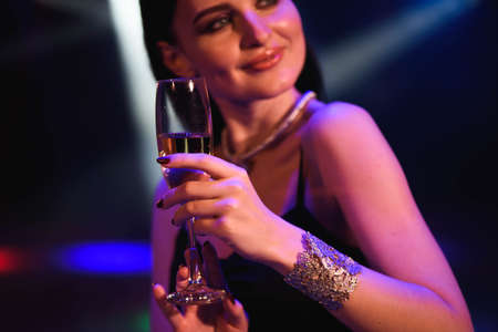 Young celebrating woman black dress, holding a glass of champagne. Party Foto de archivo