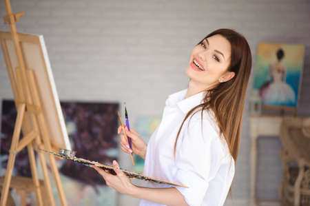 Young female artist painting picture in studio. Foto de archivo