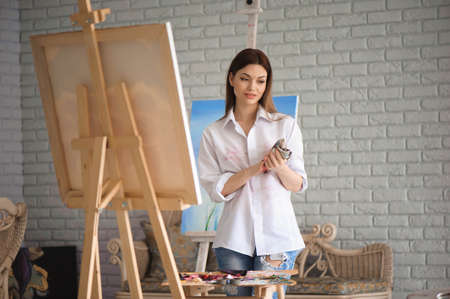 Portrait of a young student standing with painting at the studio.
