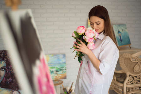Female painter drawing in art studio using easel. Portrait of a young woman painting with oil paints, side view portrait.