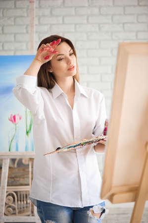 Woman paints picture on canvas with oil paints in her studio. Foto de archivo