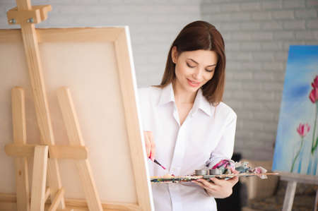 woman paints picture on canvas with oil paints in her studio