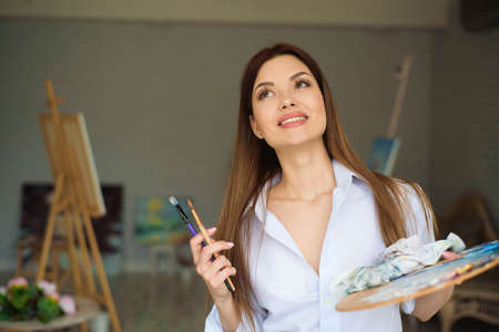 Portrait of talented young woman painting picture in art studio with inspiration.