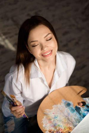 Creative pensive painter paints a colorful picture. Closeup of painting process in art workshop Creative positive woman painter paints in her studio