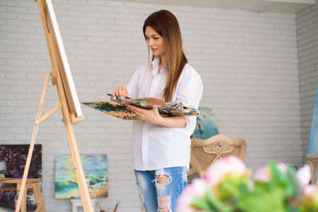 Cute beautiful girl artist painting a picture on a canvas on an easel. Studio white background. Long hair, brunette. Holding colorful brush and palette.