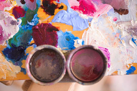 artists brushes and oil paints on wooden palette.