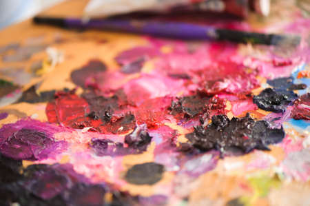 art, creativity and people concept - close up of artist with palette knife painting still life on easel at studio Foto de archivo