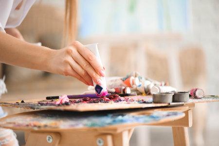 Closeup of paintbrush in woman hands mixing paints on palette. Foto de archivo