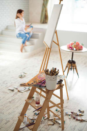 Young woman painting picture in art studio with inspiration.