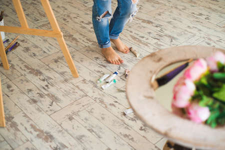 Young inspired girl choosing paint tube in light studio. Foto de archivo