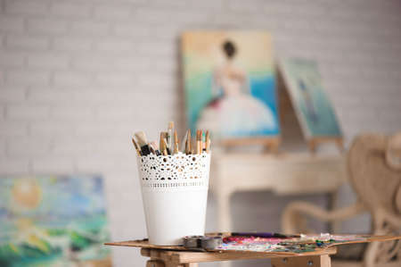 Artistic equipment: easel, paint brushes, tubes of paint, palette and paintings on work table in a artist studio Foto de archivo