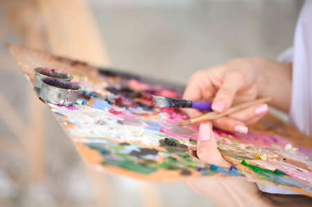 Close up of womans hand mix paints with brush in palette in art-class.