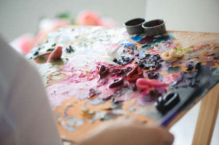 girl artist mixes oil paints on a palette.