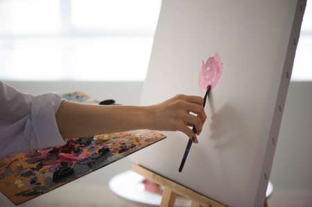 Young female student having classes at art studio, learning how to draw flowers Foto de archivo