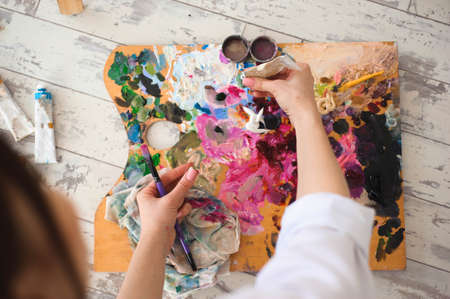 Young female student having classes at art studio, trying to mix different watercolors on cardboard. Foto de archivo
