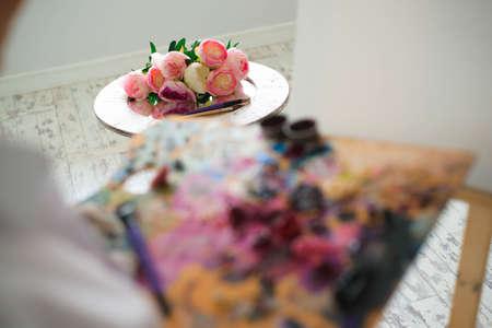 Girl artist mixes oil paints on a palette. Foto de archivo