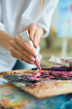 Art, creativity and people concept - close up of artist with palette knife painting still life on easel at studio.