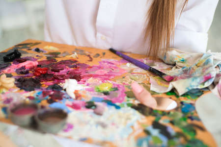 Cute girl artist paints on canvas painting on the easel. Model in the studio. Foto de archivo