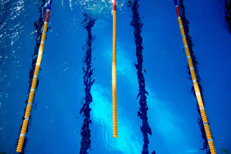 Calm water on empty swimming pool, dark lanes marks visible floor