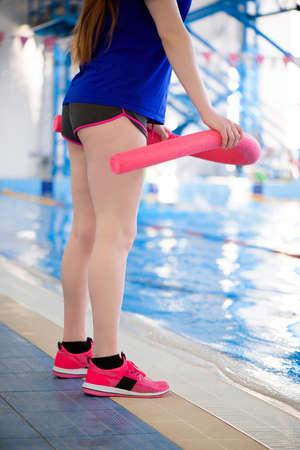 A trainer near the sports swimming pool trains aqua aerobics.