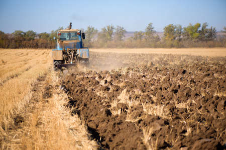 Tractor seeding directly into the stubble after the harvest with blue sky in autumn day. Standard-Bild
