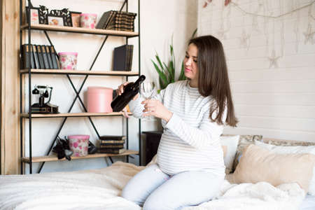 Pregnant alcoholic woman is pouring wine from a bottle into a glass and drinking.