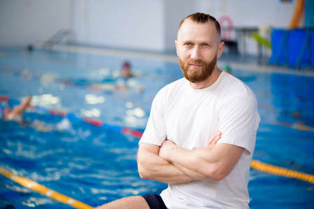 A young swimming coach watches the workout near the sports pool. Standard-Bild