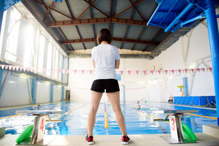 Girl coach near the sports swimming pool. Imagens