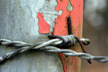 Barbed wire around a pole