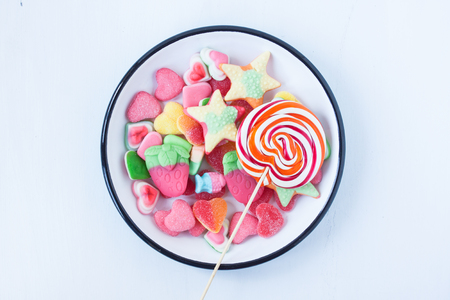 lollipop and assorted jelly candies on a white background