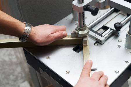 framer: Craftsman working on frame in frameshop. Professional framer hand holding frame angle. Top view.