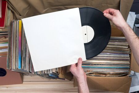 mack: Retro styled image of a collection of old vinyl record lps with sleeves on a wooden background. Browsing through vinyl records collection. Music background. Copy space. Stock Photo