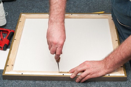 framer: Craftsman working on frame in frame shop. Professional framer hand holding frame angle. Copy space. Top view.