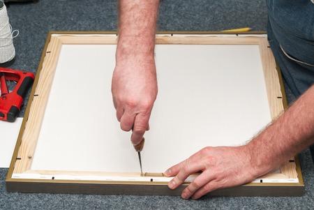 framer: Craftsman working on frame in frame shop. Professional framer hand holding frame angle. Copy space. Top view.