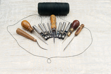 Leather craft tools on a leather background. Craftsman work desk . Piece of hide and working handmade tools on a work table. Top view. Copy space. Stock Photo