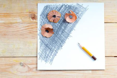 sharpened: Pencil sharpener shavings on the white paper. Back to school. Copy space.