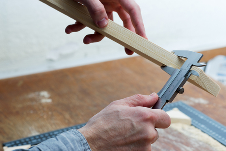 Carpenter working. Check measurement of blank. Stock Photo
