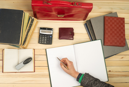 testament schreiben: Financial concept. Businessman counting profit and losses, analyzing financial results. On a wooden table books, documents, calculator, red briefcase. Lizenzfreie Bilder