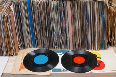 Browsing through vinyl records collection. Music background. Copy space. Retro styled image.