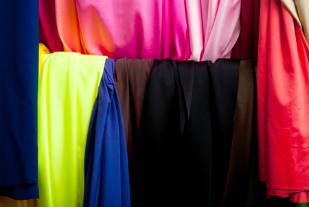 canva: Rolls of textile, cloth and tissue of various colours on the market.