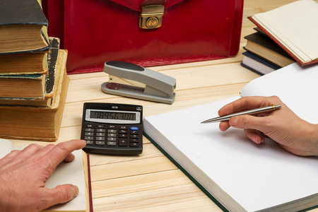 testament schreiben: Financial concept. Business partners discuss profit and losses, analyzing financial results. On a wooden table books, documents, calculator, stapler, red briefcase.