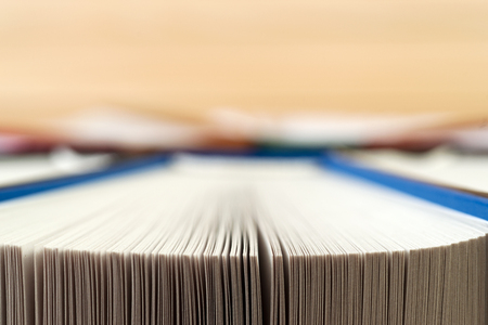 Open book, stack of hardback books on wooden table. Back to school. Copy space. Stock Photo