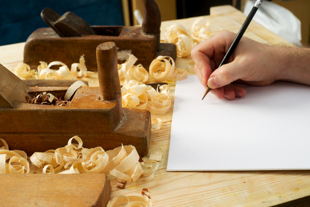 White sheet on wooden table for carpenter tools with sawdust. Copy space. Top view. Stock Photo
