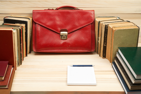 testament schreiben: Table for signing documents. On a wooden table books, documents, red briefcase.