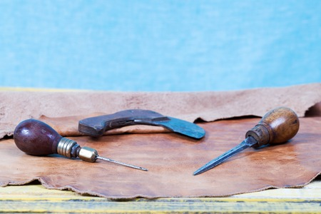 striker: Leather craft tools on a wooden background. Leather craftmans work desk . Piece of hide and working handmade tools on a work table