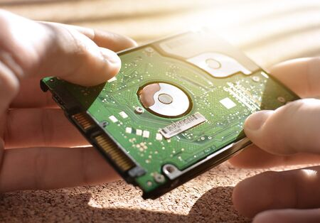 Engineering design holds the hard drive. Repair of computer equipment. Memory. Repair shop. Solar flare. Stock Photo
