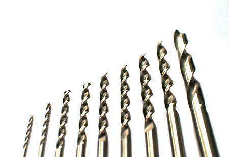 Drill bits of different sizes, isolated on white background. Close up .Instrument.