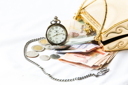 Golden clutch ,money and  vintage pocket watch ,Time and financial concept. photo