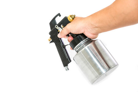 paint gun: Hand and spray gun at work Stock Photo