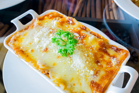 cheese platter: traditional lasagna made with minced beef bolognese sauce topped with basil leafs